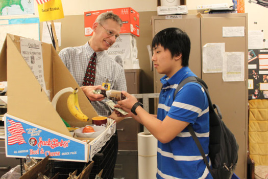 Sophomore Mark Xiong buys coffee from Doug Berglund before first lunch. Berglund sells coffee for $1.50.