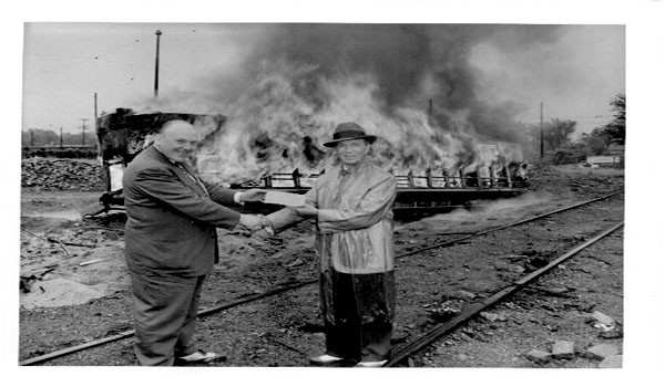Businessman James Towley and Fred Osanna,head of the Twin Cities Rapid Transit Company, shake hands and exchange money as the last of the Minneapolis streetcars burns behind them, in 1954.