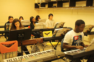 Look busy! Ms. Hippen said to students when I stepped in to take pictures. Students, like sophomores, Lydia Zewdie and Michel Lee, can start playing piano with little experience and learn to play with the class. Photo: Grace Palmer