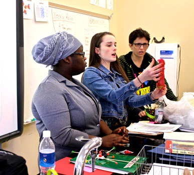 Senior Fatima Ibrahim, junior Rachel White, and sophomore Peter Tolle demonstrate how to use a condom in a middle school class at Keewaydin.