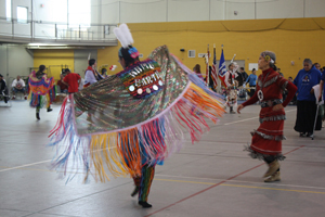 A fancy shawl dancer proudly displays her reservation, White Earth, during the Grand Entry  of the All Nations pow-wow. This part of the ceremony often includes a prayer.