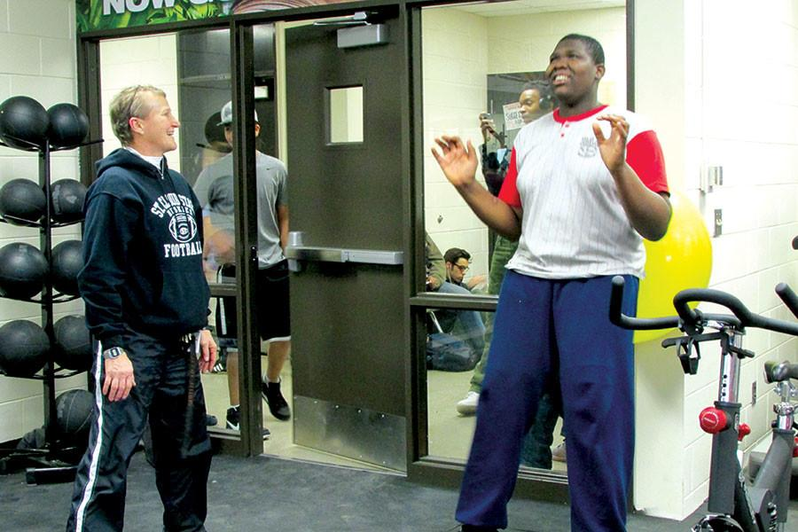 Gym teacher Carol Allery walks freshman Wisdom Kowouto through a workout in the weight room. Allery expressed disapointment when she found out that the gym requirement for graduation will be reduced to one semester for incoming freshman.