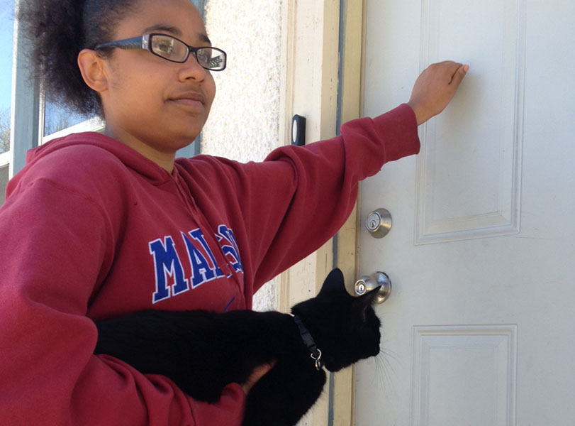Senior Alexzandrea Jackson knocks on doors in the neighborhood around South attempting to locate the cat's owner.