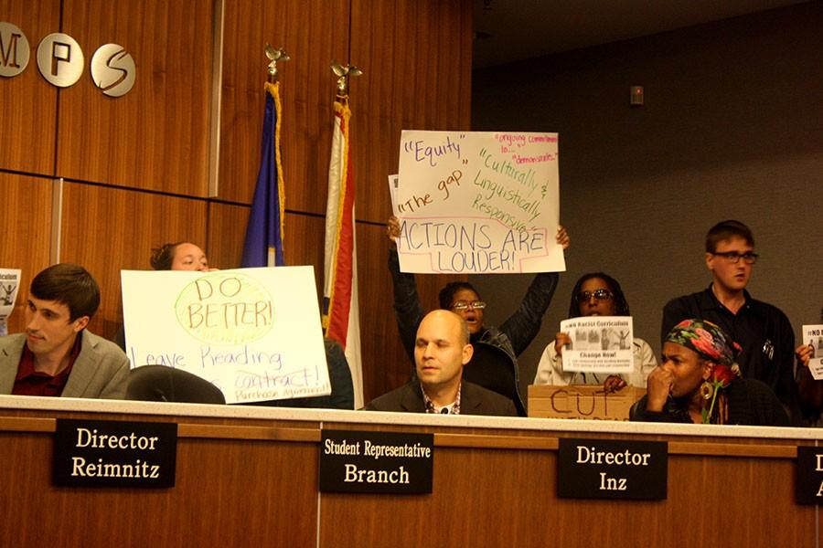 Protesters made their way behind school board members' chairs.