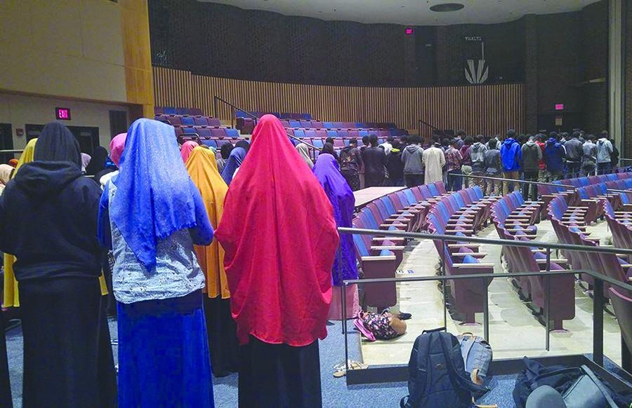 Muslim students stand during the Jumat Solat, the Friday prayer. The Muslim Student Association facilitates Friday reflection time for close to 100 students. The accomodation allows students to honor cultural and academic identities without having to prioritize one over the other.