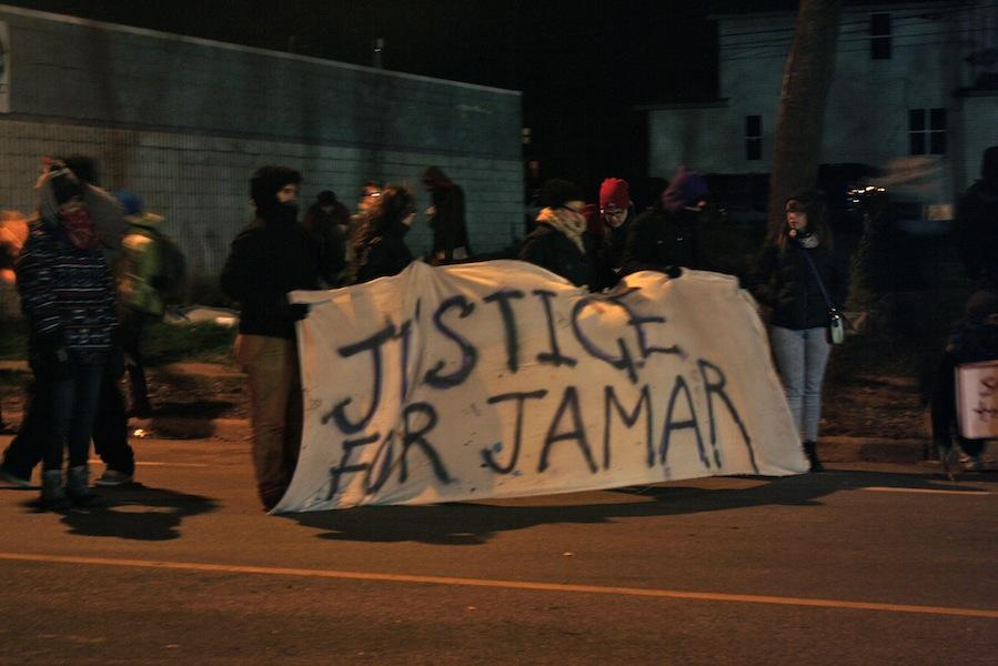 Protesters hold a #justice4jamar banner in front of the precinct