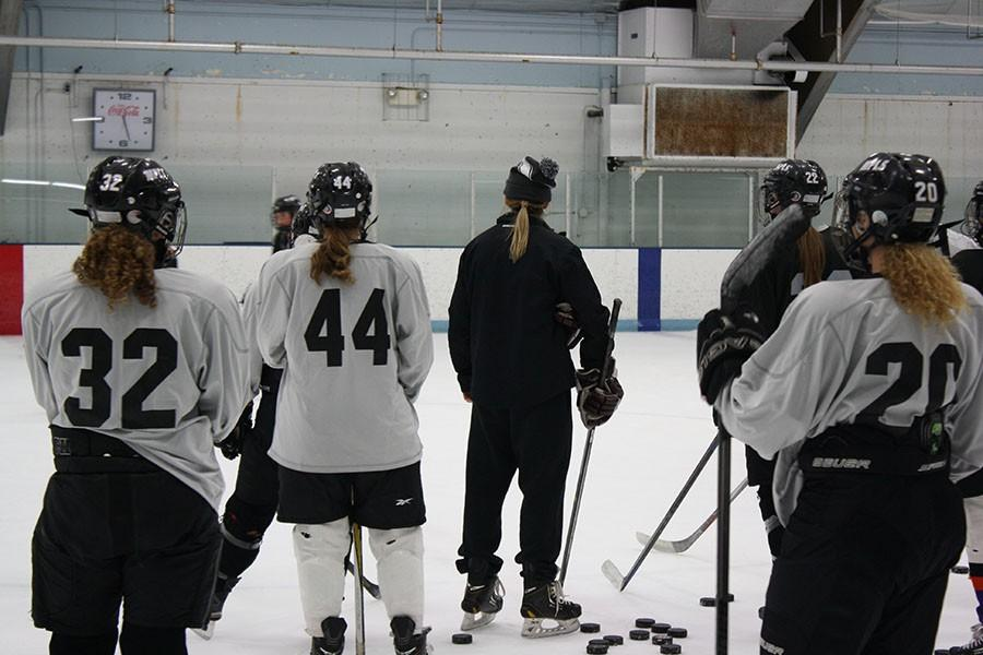 "Head varsity girls hockey coach Sarma Özmen (middle) explains a drill to her team. Özmen is a player for the Latvian National Hockey Team and aspires to be a referee in the Olympics. ""I think she raises the bar for us, but I think that's a good thing, because it really helps us get better,"" said sophomore Lilah Schulz."