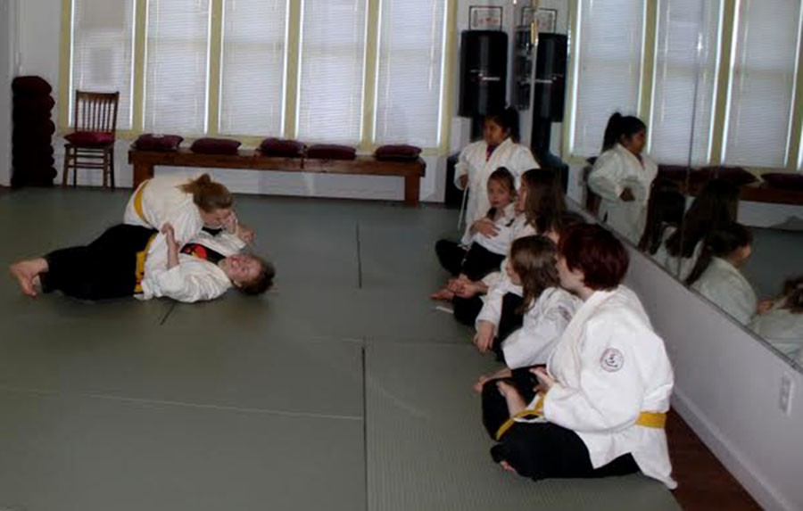"""Two girls practice their Judo skills at Five Element Martial Arts at Cedar Avenue and East 38th street. The self-defense classes at FEMA focus on the """"Five Fingers"""": Mind, Voice, Escape, Fight, and Tell. The class emphasizes """"knowing how to get out of those situations before they escalate,"""" sophomore Ingrid Zoll explained."""