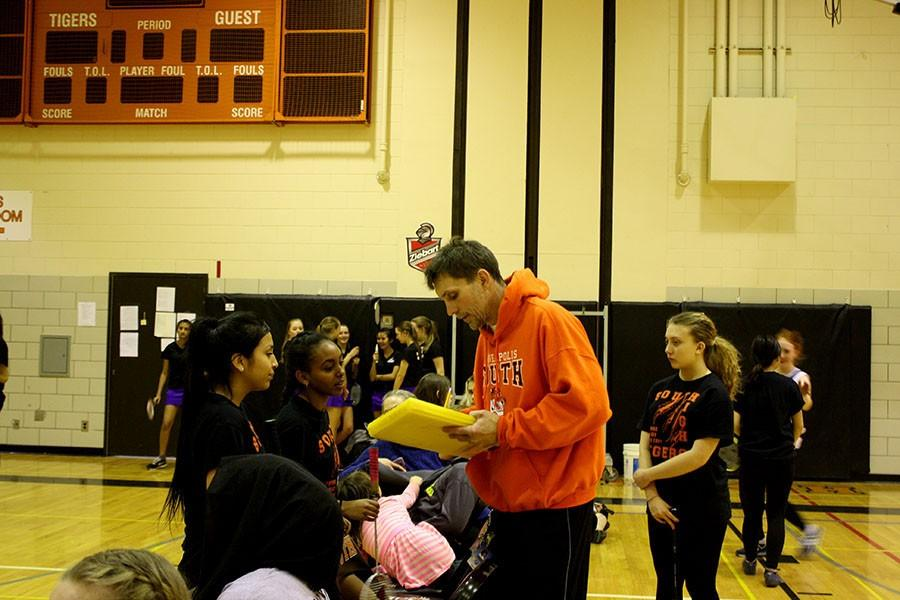 """New badminton coach Rodney Lossow discusses matches with badminton players. The team has grown largely this year due to Lossow's no cut policy.  """"It'll make the program better in the long run just because you're gonna get a girl who maybe wouldn't try out and she gonna really excel and grow."""" He explained."""