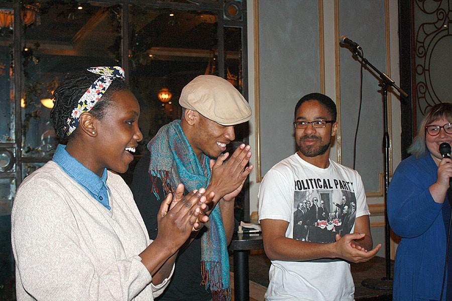 """Sarah Ogutu (left) celebrates the winner of SlamMN!'s slam on March 22nd, Donte Williams (center). Williams is now part of the 2016 national slam team, which competes on a national level in June and July. The competition aspect of slam poetry has helped artists shape their poetic voice, as explained by Williams: """"Slams have very practical ways that helps your writing...having a time limit really allows me to not waste time with language [like] what word is going to fit here."""""""