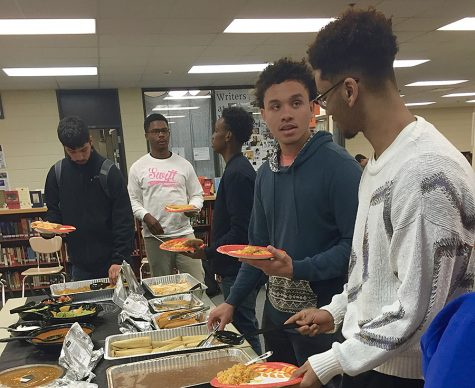 "Seniors Nate Mamo, Victor Flagg, Emilio Reyes, and Nasir Abdulkadir load their plates with La Loma food. Bowdry, who is headed to Northwestern University in Roseville, MN, credits his academic success to the ""family"" atmosphere created by his sports teams and friends."