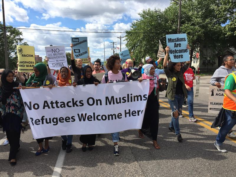 Photo Credit: Eli Shimanski A banner being supported by Ahalm Mussa. Aishah Mohammad and Ndolo Elate, three South students that participated in the march.