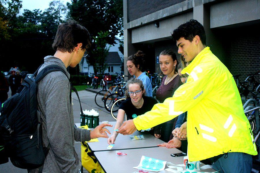 Senior and Green Tigers member Marco Dregni hands a student biker a mystery Nickelodeon Universe pass on Bike to School Day. Isabel Strebe and Livia Lund, co-presidents of Green Tigers, are shown.