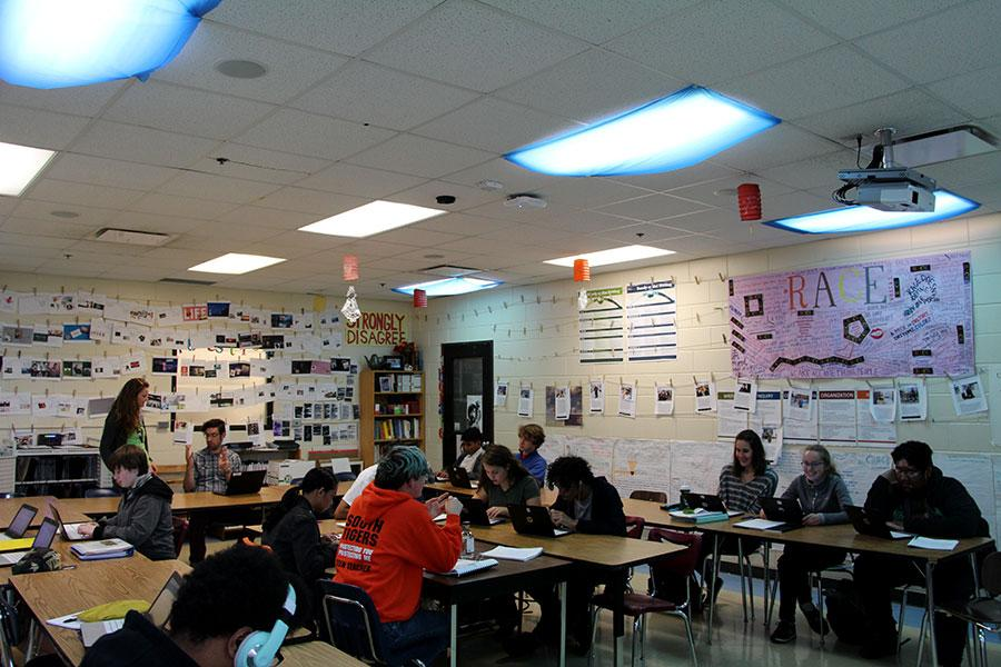 Students work quietly under the blue cloths Darin Doty put up to dim the harsh light.