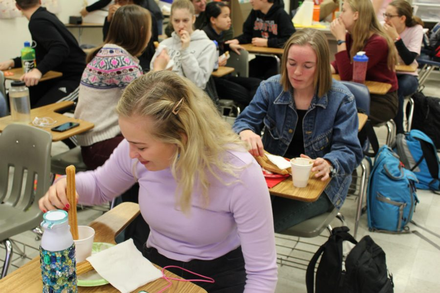 """South High seniors Grace Larson, and Lauren Van Doren enjoy their tasty churros by dipping them in """"Mexican Hot chocolate"""" provided by their teacher Profe Luz Arias. Photo: Izzy Willette"""