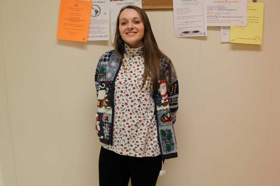"Senior Lily Mooney sports one of her Christmas sweaters, as she does everyday during the month of December.  ""I started wearing them in 8th grade,"" Mooney remembered. ""I only owned three and every year since then I've started getting more sweaters, vests, shirts and earrings all that kind of stuff."" Photo: Katherine Lundquist"