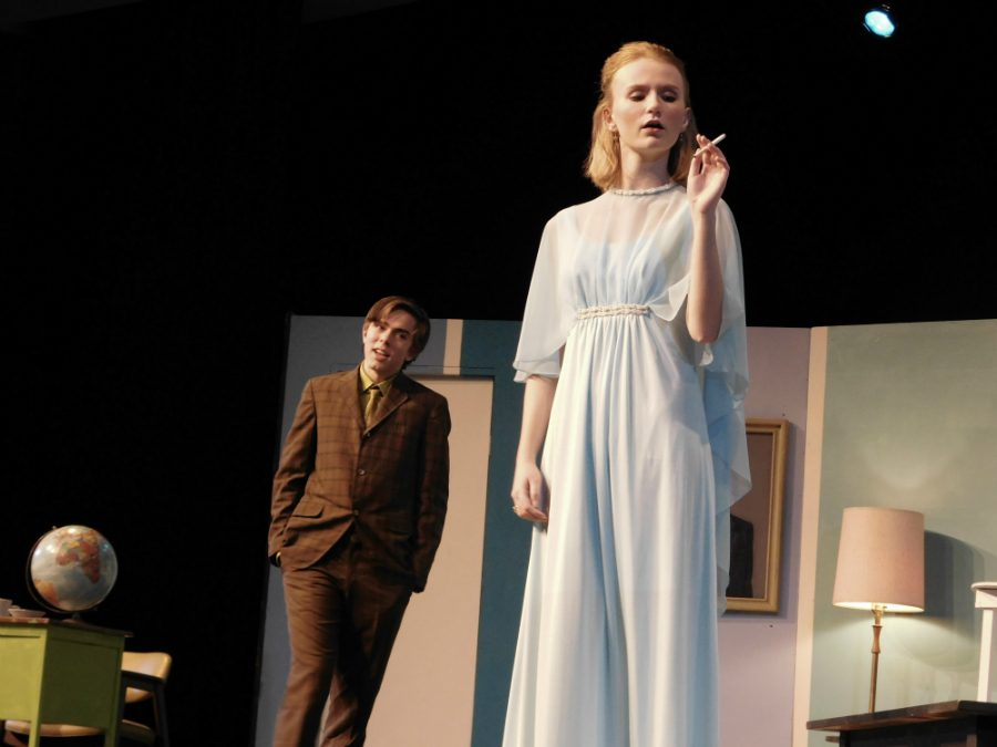 Gretchen (Astrid Berger), smoking a cigarette while Robert (Nathanial Hasse) flirts with her.
