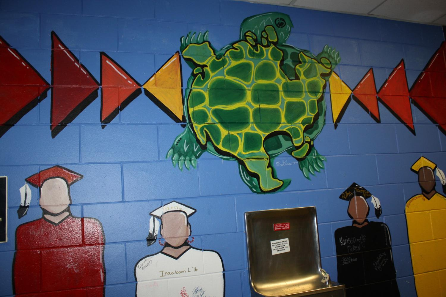 "Breanna Green painted a ""graduate"" mural on the wall in the All Nations hallway last year. She won the ""Dream Warriors scholarship"", for using her passion for art to define what it means to be a leader. Oftentime, her art incorporates Native American traditional aspects along with modern ones. As All Nations social studies teacher Vincent Patton said, ""she has a lot of traditional aspects to her art but she is also intertwining her new modern contemporary urban Native American flair."" Photo: Sophia Manolis"