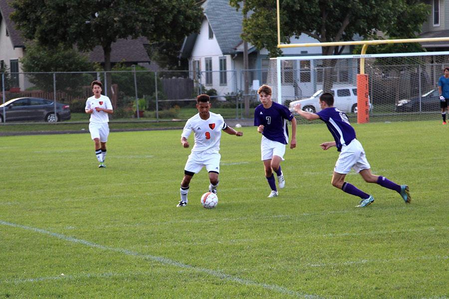 Senior Nate Kange working his way around two Southwest defenders (Men's Varsity)