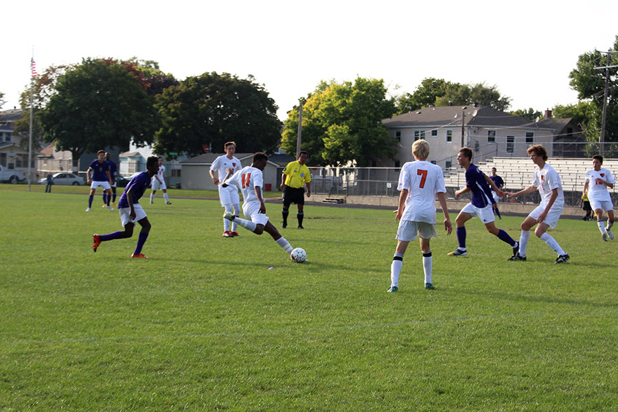 Senior Mohamud Mohamud  winding up to pass the ball to  his teammate (Men's Varsity)