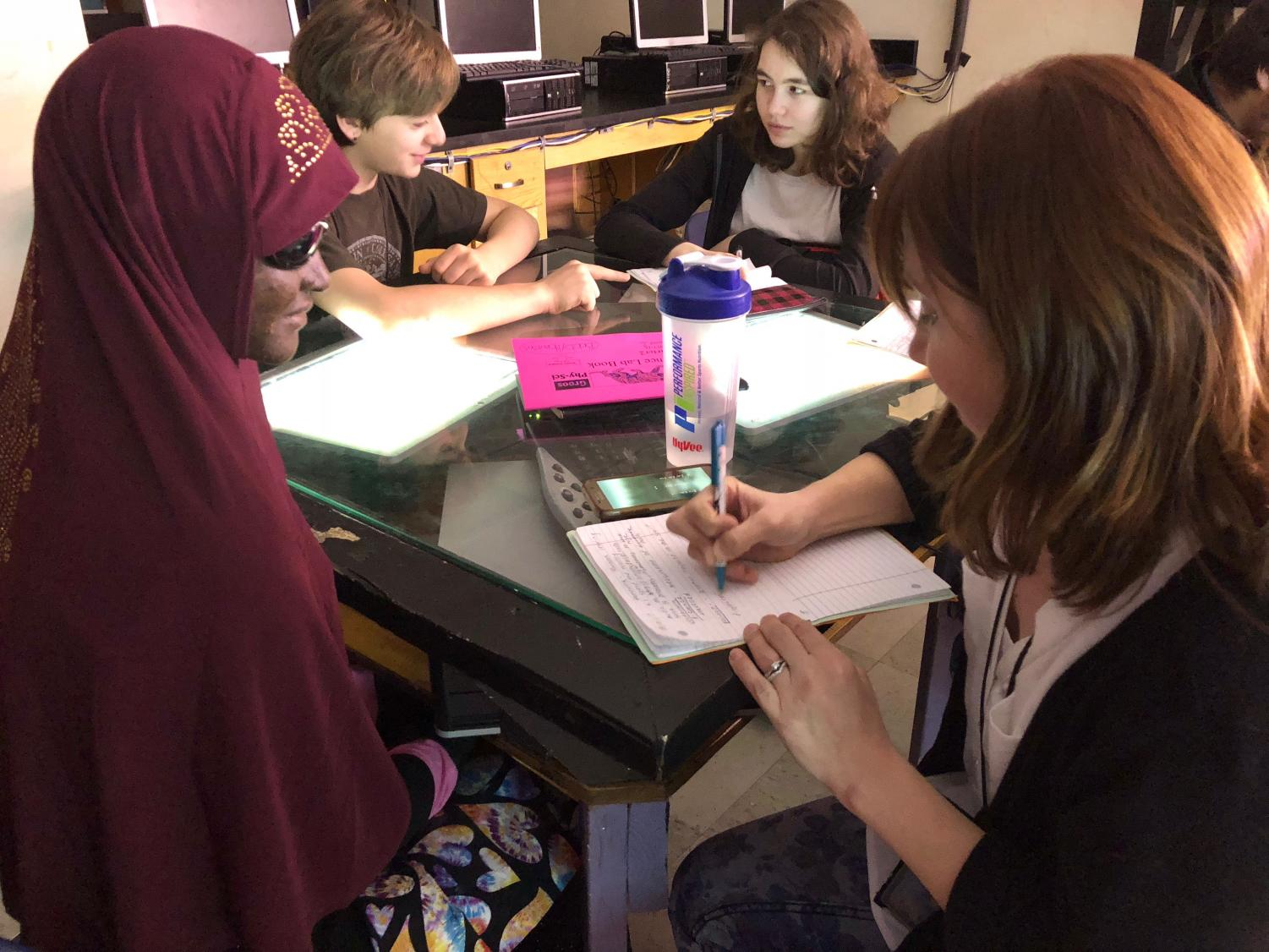 "Pictured above freshman Haney Mohamed and her SEA (special education assistant), Laura Anderson with students Sasha Rapacz (left) and Beatrice Kennedy-Logan (right) in the background. In this photo, Anderson copies definitions from the board into Mohamed's notebook and explains the information that she cannot see. ""When teachers write on, let's say a white board: visually impaired people cannot see the whiteboard. The SEA's explain what is written, they tell them what it says,"" said Haney Mohamed. This extra help is vital for a successful schooling experience for students with visual impairments. Picture: Kinsley Wilcox-McBride"