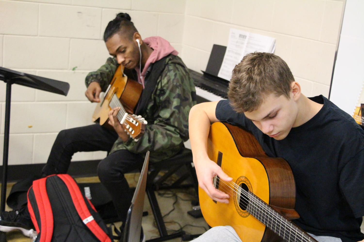 """Omesh Shiwmangal, on the left, and Sam Guindon practice an original composition for a relief album music teacher Sarah Minette started. The profits of the album will go towards the Red Cross. """"It's a cool experience to mix an album and it puts the project in the hands of the students,"""" said Minette."""