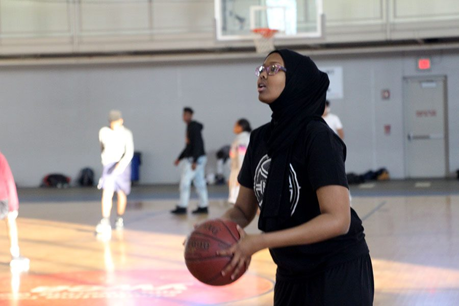 "Freshman and member of South's B-Squad Basketball team Rahma Farah lines up for a shot at practice. With South getting sport hijabs for the first time this year, it's easier for her and some of her teammates to practice and play in games. Farah explained, ""Without the sport hijabs it would be so difficult to play [in practices and games]."" Photo: Cece Kaufmann"
