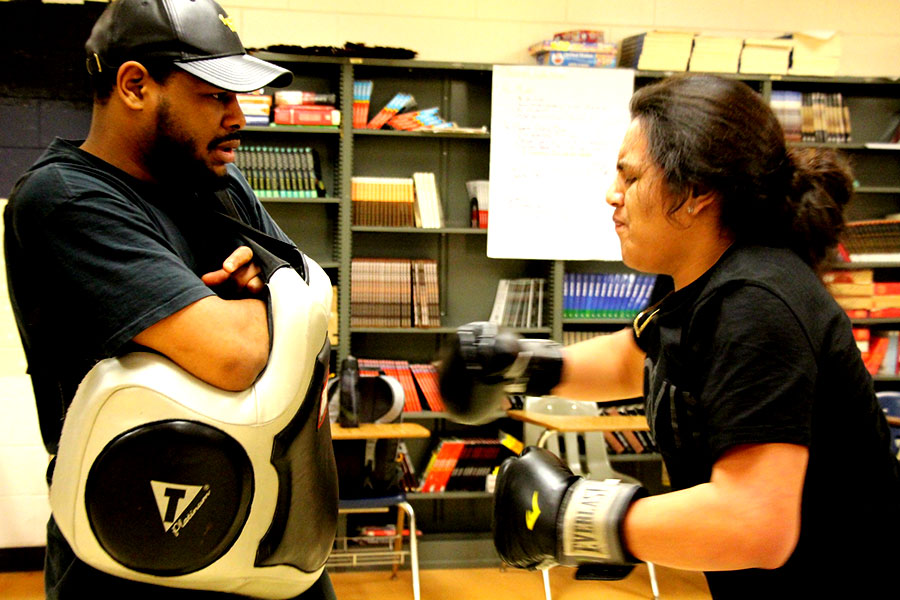 "Andrew Fohrenkam practices his punches against coach Cerresso Fort. Fort finds that boxing ""takes techniques and skills and you got to use your mind and brain to think. It's good to be healthy.""  Picture: Gabe Chang-Deutsch"