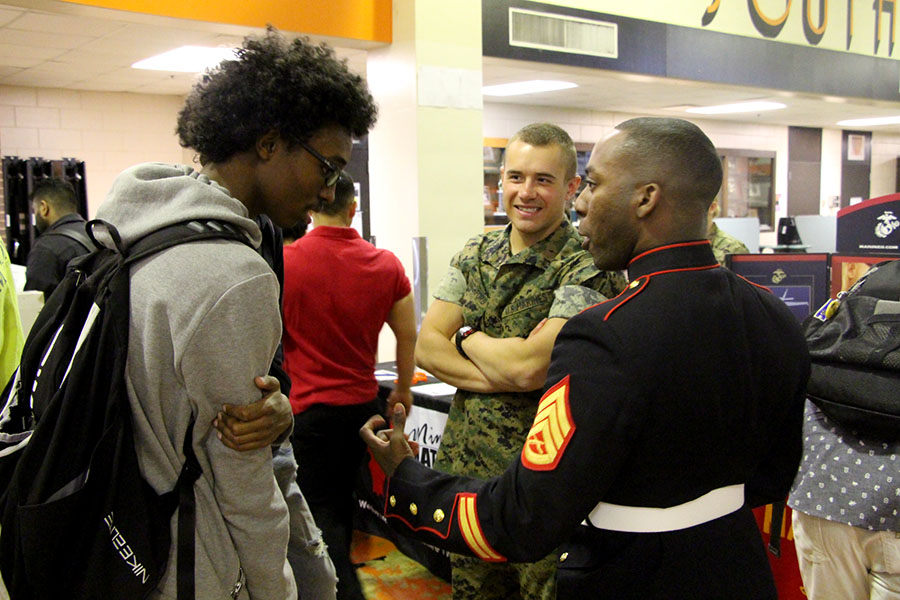 Staff Sergent Clevon Clarke and Private First Class Griffin Ruthford, talk to junior Abdifitah Farah about the opportunity that the Marine Corps provides. The Marine Corps are one of the six branches that possible enlistees can choose to go into.