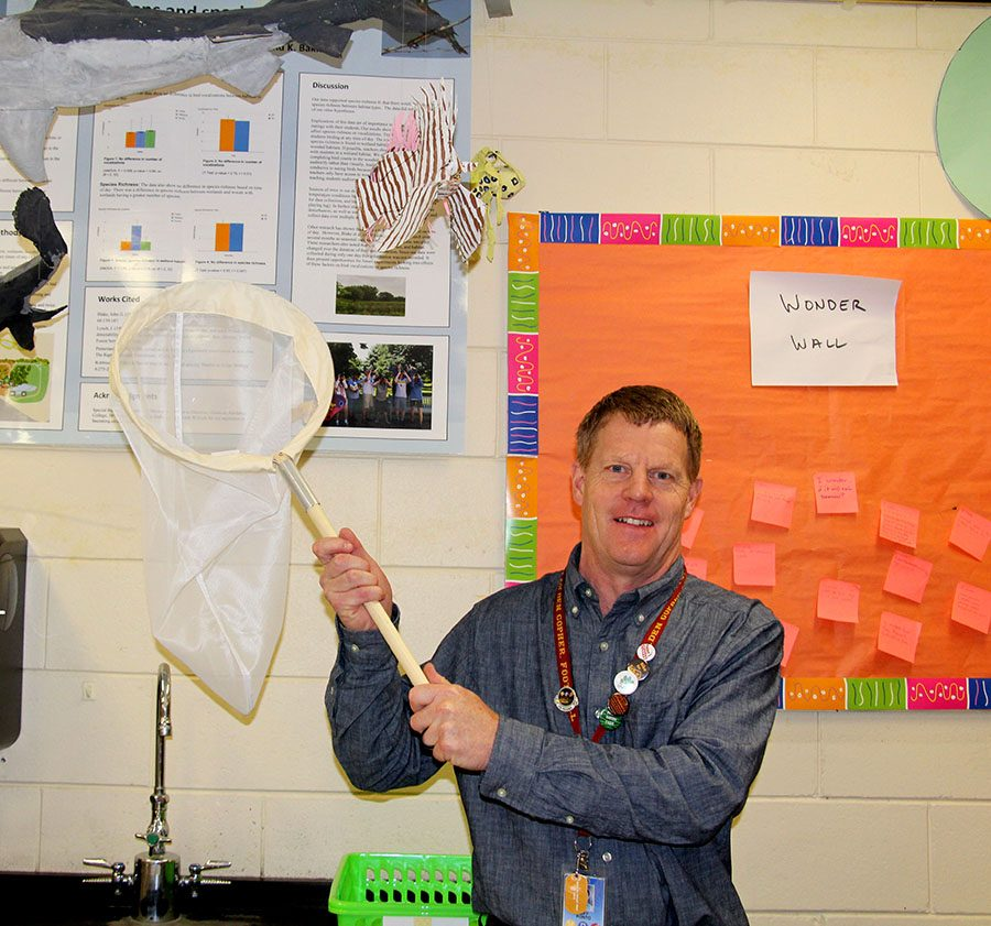 Biology teacher Jeff Ponto proudly displays a butterfly and dragonfly net supplied by the Driven To Discover program. ¨ We've written grants, gotten equipment...the kids are out catching dragonflies with nets that came with this program.¨ Photo: Norah Austin