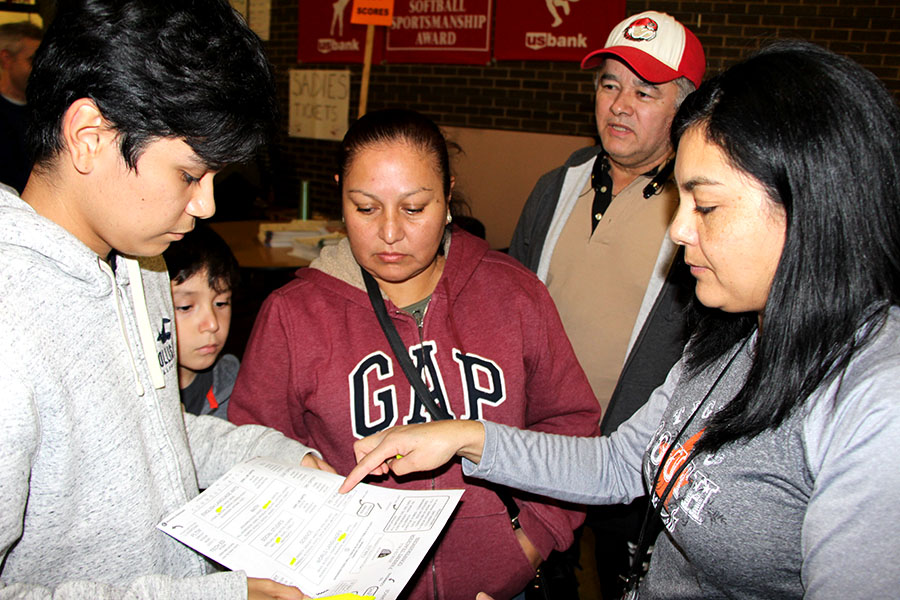 "Esmeralda Duran-Silvan, South's Spanish and English speaking parent liaison, helps a Spanish-speaking family at parent-teacher conferences. Because of the lack of allocated resources for interpreters and services for non-English speaking families, there usually isn't enough interpreters for all of the families that need one. ""You're going to have a far longer conversation with an English speaking family than you are with a translator… You know that there's other people waiting for them,"" said Alex Endeshaw, chair of the Equity team at South."