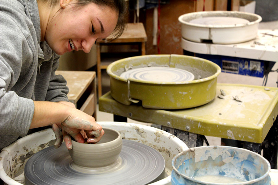 "Elizabeth Webster throws (the process of making something on the wheel) a bowl in the ceramics room, ""it's like a second home, I spend so much time there,"" she says."
