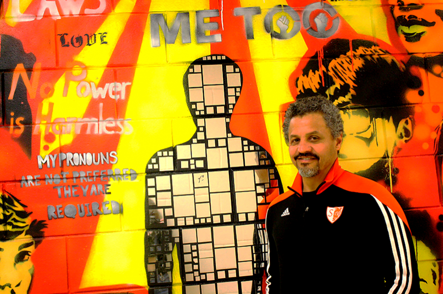 "Above is Mr. Aponte with his favorite mural that has gone up in his time as Principal at South.  ""I'm hoping that we can continue working on a lot of the things that he was responsible for in his time at South… I'm hoping that some of the visibility for particular groups of students and some of the work that we've been doing to try to improve things for them will continue to happen,"" said history teacher Joshua Fisher. Aponte considers South the ""pinnacle of his career"" and is proud of improvements made, including South's various murals."
