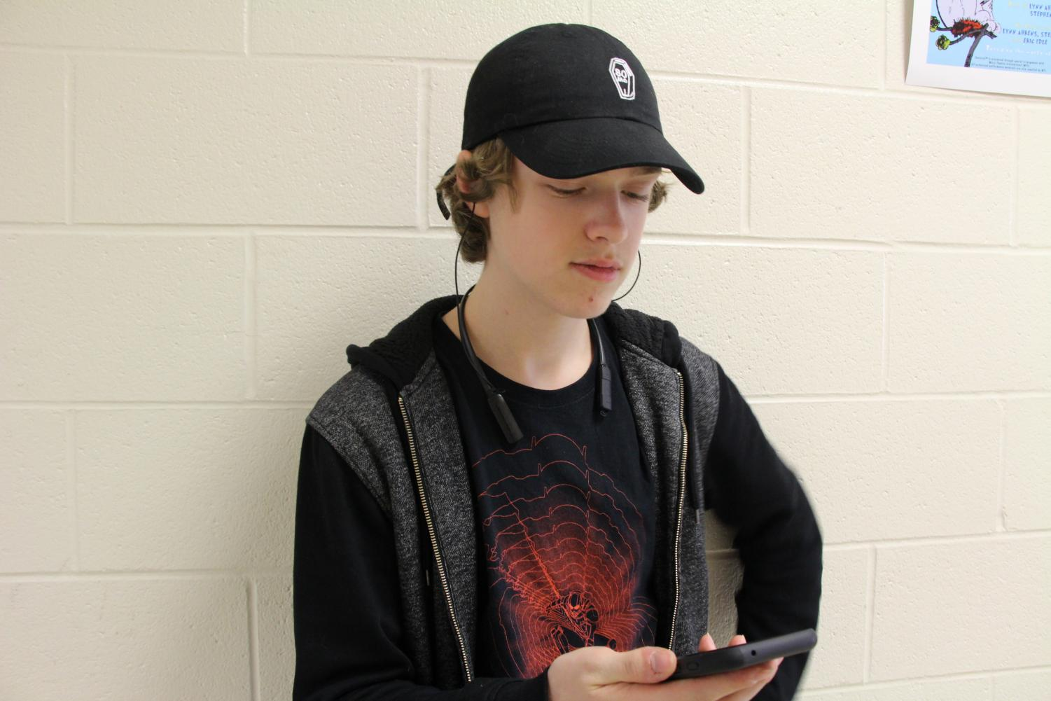 "Aidan Sumner-Malmgren, a bassist and sophomore, listens to music on his headphones in the third floor of South high school. ""I have no idea [what I'd do without a music app], I probably wouldn't listen to music,"" said Sumner-Malmgren."