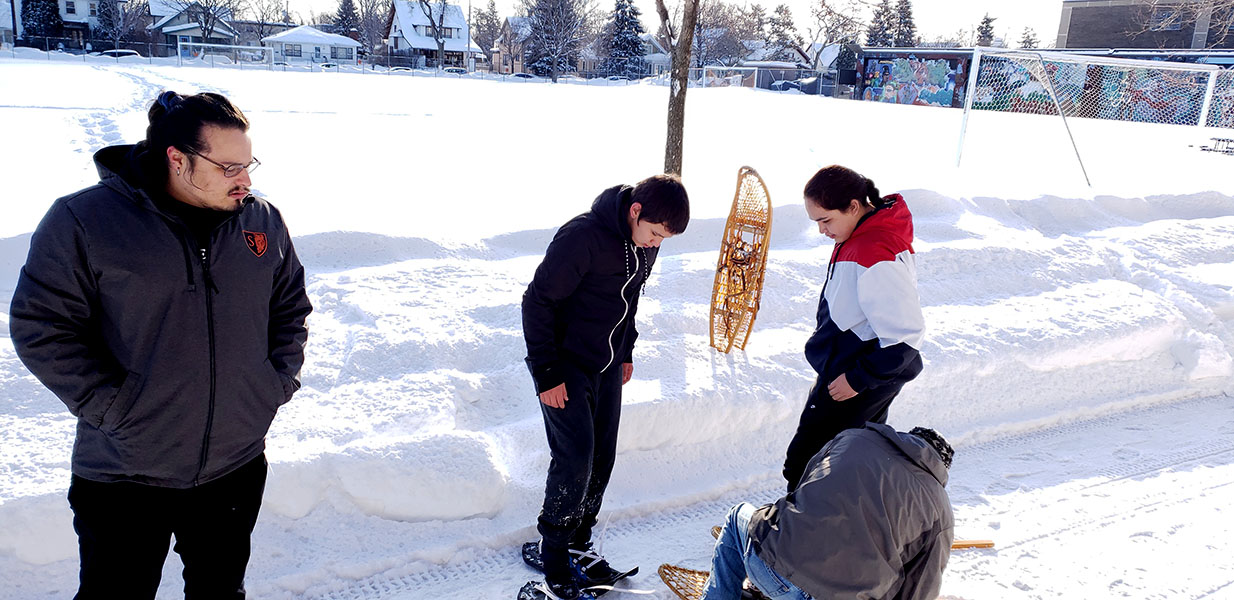 "Students put on previously made snowshoes near the field outside of South. In the coming weeks students in the All Nations program will be creating their own. ""It's a very culturally applicable project, really our students have kind of been into it, and I think that they can learn a lot from it,"" said Vince Patton, the All Nations social studies teacher."