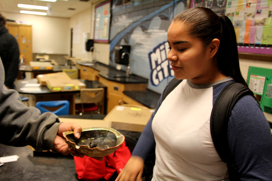 All Nations sophomore Ogi Moose receives a shell containing burning sage from Ojibwe teacher Bezh Butler. Students can take part in smudging every school-day morning during first hour.