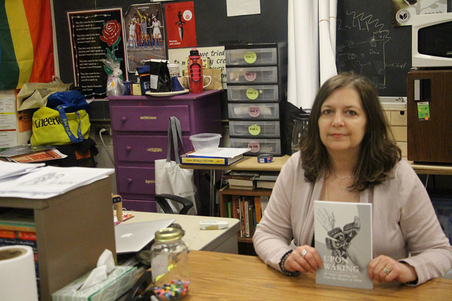 """South social studies teacher Ms. Lanik shown with a copy of her book. """"We can create a new normal - a new society where people who abuse are held accountable for their actions"""", says Ms. Lanik."""