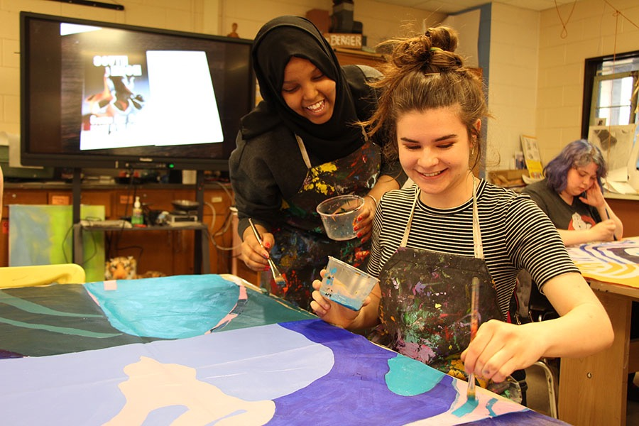 South High students Nasra Hassan and Frances Levy are just a few of the visual art students working together to paint the new mural for South. The mural that they are working on will be replacing the mural that is alongside the practice field by the end of June.