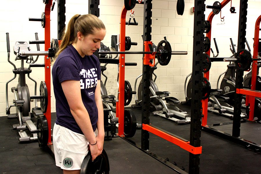 "Emma Dinger, a junior on the women's soccer team, does calf raises at a weightlifting session before school. Many sports teams, including soccer, swimming, and badminton, have started holding practices in the morning to better accommodate schedules. ""Rather than doing practices at 6 o'clock, after school, it's just easier to do it in the morning. And I actually like doing it in the morning, because then I have the afternoons free,"" said freshman Madeline Leventhal, a player on the Badminton team."
