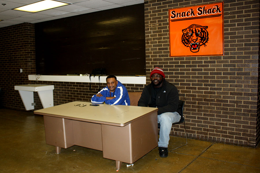 "Cedric McKinley and Russell Smith working in their usual spot by the snack shack. ""I feel like the position we're in right now, I think, hurts us more because now we do have a relationship with the kids that we used to have but it's not the same because we're not walking down the hallways, we're not telling them 'hey go to class and go do what you need to do to get the job done,"" said McKinley."