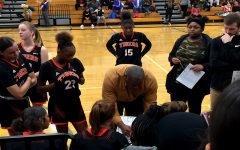"New girls varsity basketball head coach Ricky Hill (middle) draws up a game plan during the December 19th match vs. North High School. ""I started coaching my daughter, and that's how I got into coaching girls basketball."""