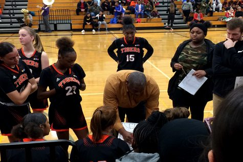 "New girls varsity basketball head coach Ricky Hill (middle) draws up a game plan during the December 19th match vs. North High School. ""I started coaching my daughter, and that"